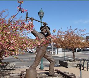 Statue of a worker swinging a hammer on a railroad tie